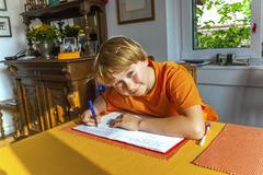 Boy prepares his homework for school Stock Photos