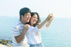 young man and woman take a photo by smart phone at sea side use for new peopl - stock photo