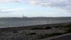 Stoney beach at Lee on Solent view towards Fawley Power Station & Oil Refinery Stock Footage