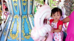 Little cute asian girl sitting on carousel with take care of mother - stock footage
