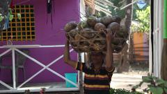 INDIA, GOA - 2012: Indian man carries a basket of coconuts on his head Stock Footage