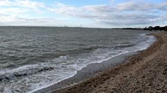 Calm waves breaking on Lee-on-the-Solent beach. Fawley on the horizon Stock Footage