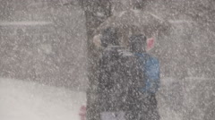 People walking in blizzard snow wind and cold weather in major winter storm Arkistovideo