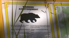 DANGER bear warning sign zoom reveal to forest trail Stock Footage