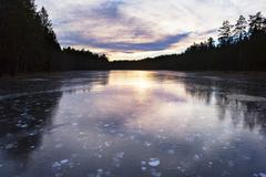 Idyllic and icy lake in sunset Stock Photos