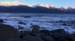 Snow Capped Peaks and Ocean Waves Crashing to Rocky Alaskan Coastline Stock Footage