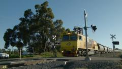 Freight Train Passing By A Railway Crossing Stock Footage