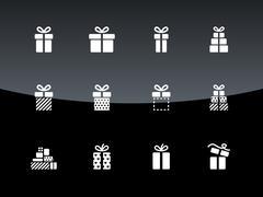 Christmas gift box icons on black background. - stock illustration