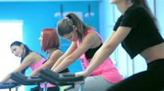 Athletic girls pedaling on the simulator - stock footage