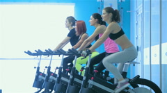 Four friends athletes pedaling on a stationary bike at the gym show thumbs up - stock footage