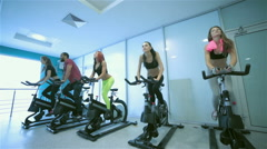 Friends pedaling and looks in front of a stationary bicycles at the gym - stock footage