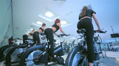 A group of girls female athletes on a stationary bike Stock Footage
