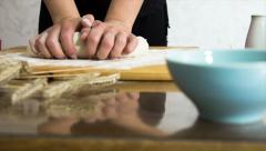 Female hands in flour kneading dough on table, dolly shot Stock Footage
