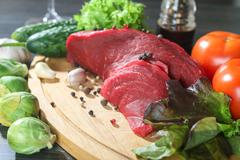 raw beef meat with vegetables on wooden table - stock photo