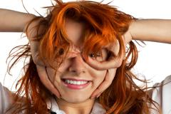Red-haired girl makes out of its hands symbolic glasses Stock Photos