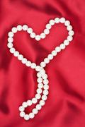 Symbolic heart on a red fabric Stock Photos