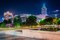 reflecting pool and buildings at night, at olympic centennial park at night i - stock photo