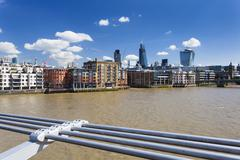 view from the millennium bridge in london to the city with several new skyscr - stock photo