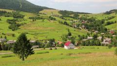 Beautiful green hills and village in Carpathians, Ukraine - stock footage