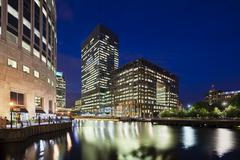 the modern canary wharf quarter with its banks and skyscrapers at night - stock photo