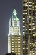 Stock Photo of the old woolworth building next to other skyscrapers in new york at night