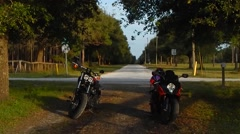 Cruiser sitting next to crotchrocket on farm road Stock Footage
