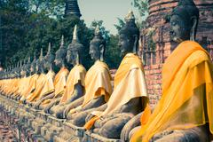 Aligned buddha statues at wat yai chaimongkol ayutthaya, bangkok, thailand Stock Photos