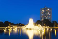 the famous europaplatz fountain in aachen, germany at night with a highrise i - stock photo