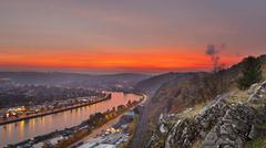 View over the meuse to huy in belgium during a fiery red sunset Stock Photos