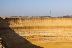 a steep lignite pit mine wall in warm evening light - stock photo