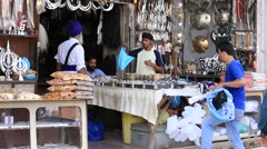 Sikhs and indian people in the gift shop next to Golden Temple.  Amritsar, India Stock Footage