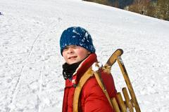 Boy is carrying his sledge Stock Photos