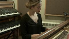 Beautiful girl playing the piano in a recording studio light slow motion Stock Footage