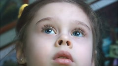 Face of a cute little girl watching TV with great interest Stock Footage