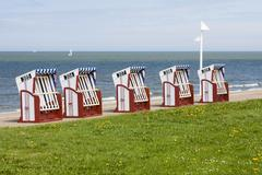 Typical beach chears also known as strandkorb by the beach in norderney, germ Stock Photos