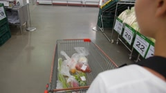 Woman Pushing a Shopping Trolley in Supermarket. Stock Footage