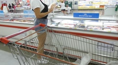Woman Choosing Food Products with Shopping Cart in Grocery. Stock Footage