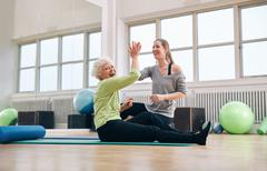 senior woman rejoicing health success with her instructor - stock photo