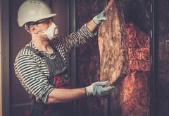 Builder in protective wear applying material on a wall Stock Photos
