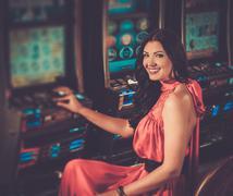 Beautiful woman in red dress playing slot machine Stock Photos