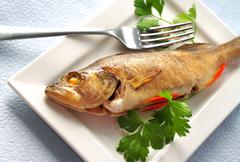 Perch baked in foil with parsley Stock Photos