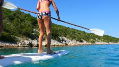 HD Slow-Mo: Playful Teen Paddle on Surfboard - stock footage