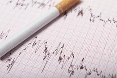 Cigarette on ecg printout Stock Photos