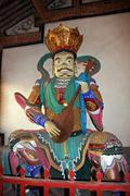 colorful statue of heavenly king at  chinese buddhist temple - stock photo