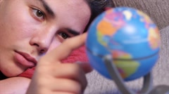 Young teen dreaming by turning a land Globe Stock Footage