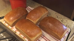 Fresh loaves of bread removed from bread pans Stock Footage