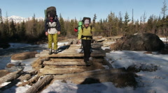 Tourists with large backpacks passing the mountain river, old wooden bridge Stock Footage