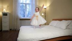 Little fidget. Cute little girl in white dress jumping on the bed in the bedroom Stock Footage