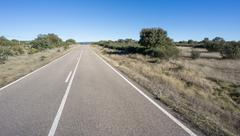 Straight road with blue sky - stock photo