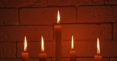 Stock Video Footage of 4K UHD. Five candles in the candlestick on a brick wall background.